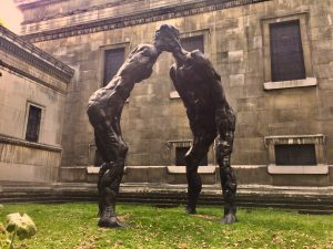 Photo image of 'Brothers', a sculpture by David Breuer-Weil which depicts two figures leaning in and joined by the head. The sculpture is installation in the church gardens at St Pancras, London.