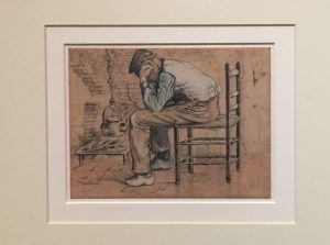 Image of sketch by Van Gogh titled 'Worn out'. Man leans on his knees holding his head in his hands, sitting on a wooden chair.
